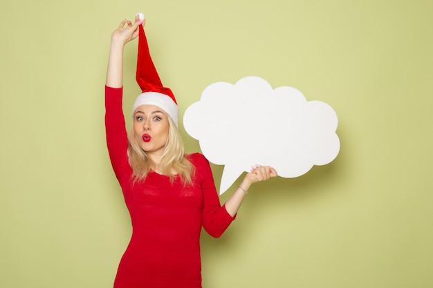 緑の壁に大きな白い看板を持っている正面図きれいな女性クリスマス雪写真感情新年