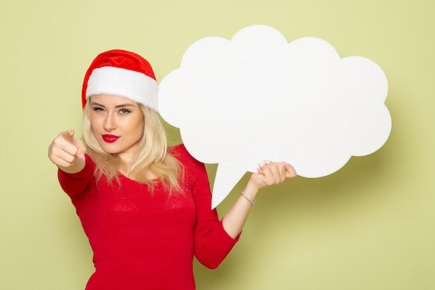 正面図緑の壁に大きな白い看板を保持しているきれいな女性クリスマス雪写真休日新年