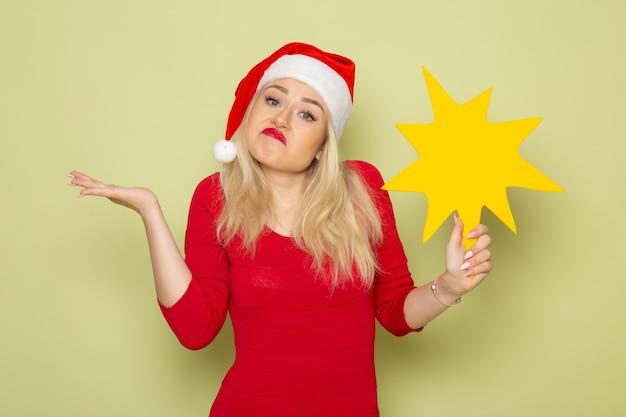 正面図緑の壁に大きな黄色の図を保持しているきれいな女性クリスマスの感情雪新年色休日