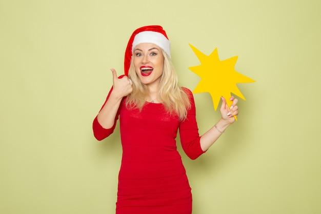 緑の壁の色の休日の感情雪新年クリスマスに大きな黄色の図を保持している正面図きれいな女性