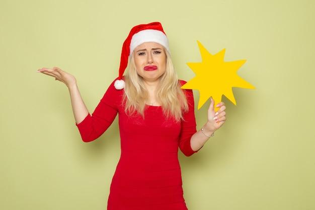 녹색 벽 크리스마스 감정 눈 새해 색상 휴일에 슬픈 얼굴로 큰 노란색 그림을 들고 전면보기 예쁜 여성