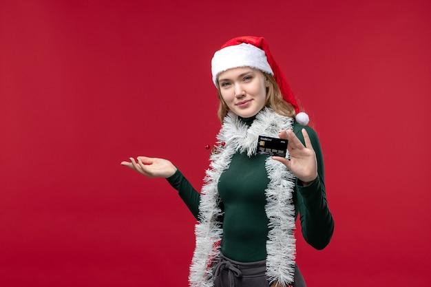 Вид спереди красивая женщина держит черную банковскую карту на красном фоне