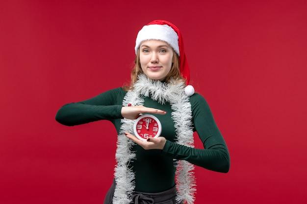 明るい赤の背景に時計を保持しているきれいな女性の正面図