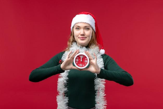 Вид спереди красивая женщина держит часы на красном фоне