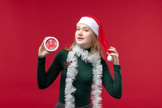 Vista frontale piuttosto femminile che tiene orologio su sfondo rosso