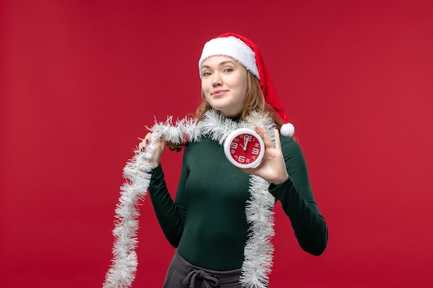 Front view pretty female holding clock on a red floor red new year holiday christmas