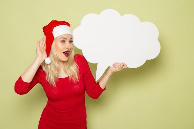 Vista frontale bella femmina azienda a forma di nuvola segno bianco sulla parete verde natale neve foto vacanza emozione capodanno