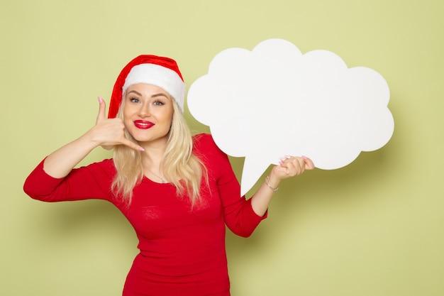 Vista frontale piuttosto femmina che tiene il segno bianco a forma di nuvola sulla parete verde natale neve foto vacanze emozioni anno nuovo