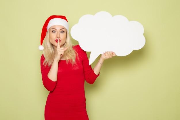Vista frontale piuttosto femmina che tiene il segno bianco a forma di nuvola sulla parete verde natale neve foto vacanze emozione nuovo anno