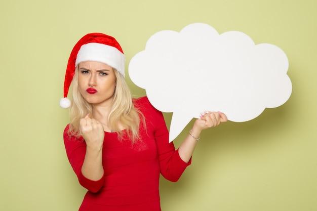 Вид спереди красивая женщина держит белый знак в форме облака на зеленой стене рождество фото праздник эмоция новый год