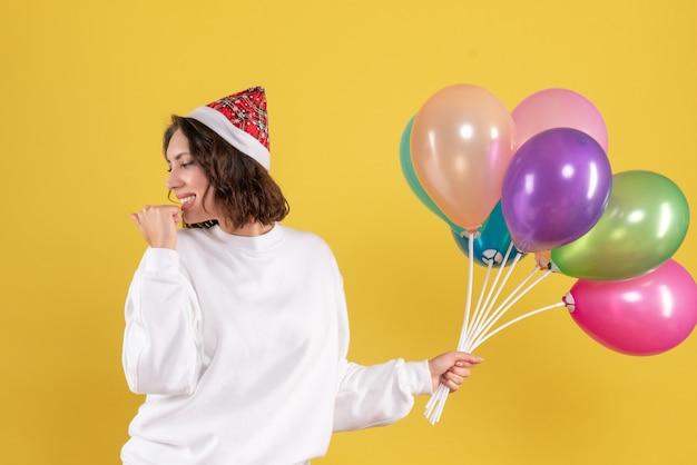 黄色のカラフルな風船を保持しているきれいな女性の正面図