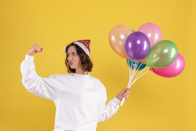 Front view pretty female holding colorful balloons on yellow
