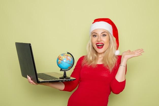 Вид спереди симпатичная женщина держит маленький земной шар и ноутбук на зеленой стене рождественский цвет снежные праздники новогодние эмоции