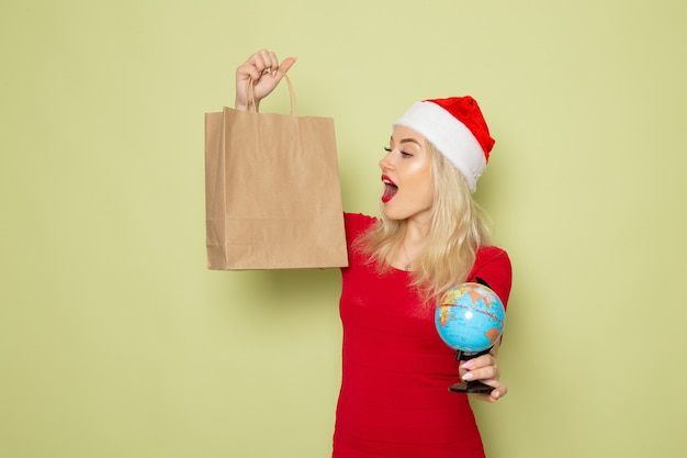 Вид спереди симпатичная женщина держит маленький земной шар и пакет на зеленой стене рождественский цвет снег праздник новогодние эмоции