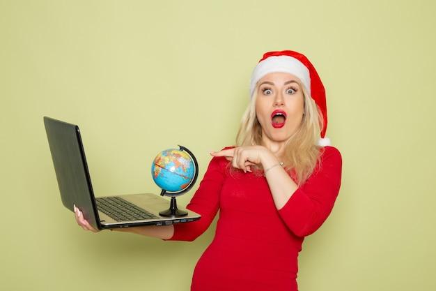 正面図きれいな女性が小さな地球儀を保持し、緑の壁にラップトップを使用してクリスマス色雪の休日新年の感情