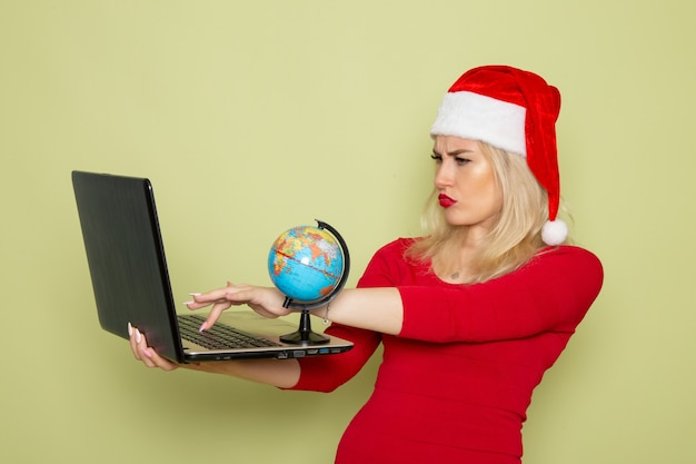 Front view pretty female holding little earth globe and laptop on green wall christmas snow holiday new year emotion