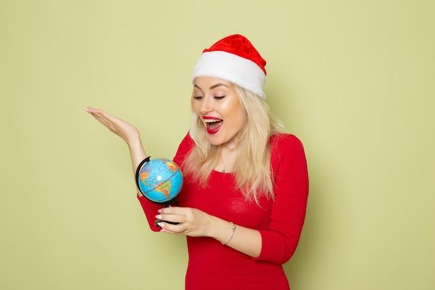 녹색 벽 휴일 크리스마스에 작은 지구 글로브를 들고 전면보기 예쁜 여성