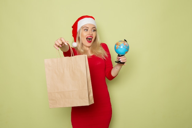 Front view pretty female holding little earth globe and package on a green wall color snow holiday christmas new year emotion