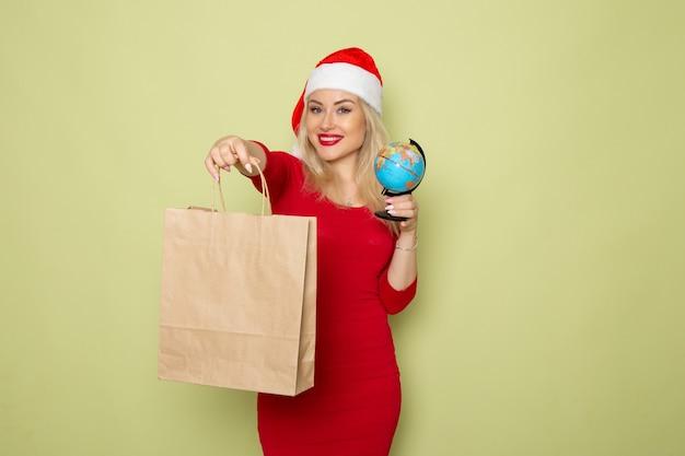 Vista frontale bella femmina che tiene piccolo globo terrestre e pacchetto sulla parete verde colore neve vacanze natale capodanno emozione
