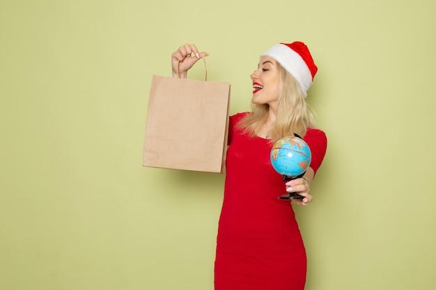 Vista frontale bella femmina che tiene piccolo globo terrestre e pacchetto sulla parete verde colore neve vacanze natale capodanno emozioni