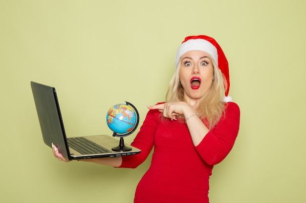 Front view pretty female holding little earth globe and using laptop on green wall christmas color snow holiday new year emotion