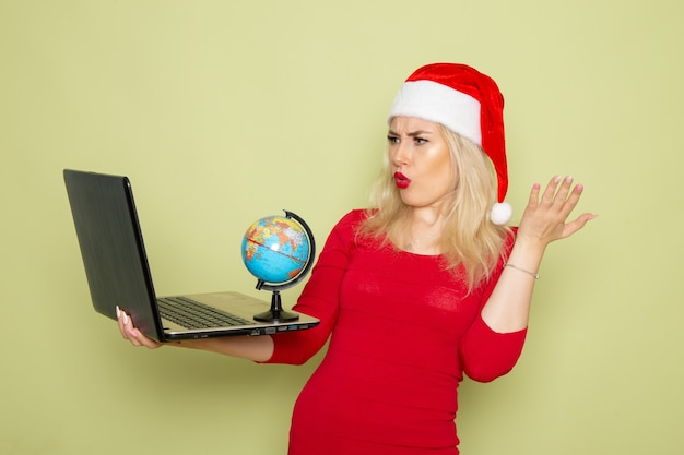 Front view pretty female holding little earth globe and using laptop on green wall christmas color snow holiday new year emotions