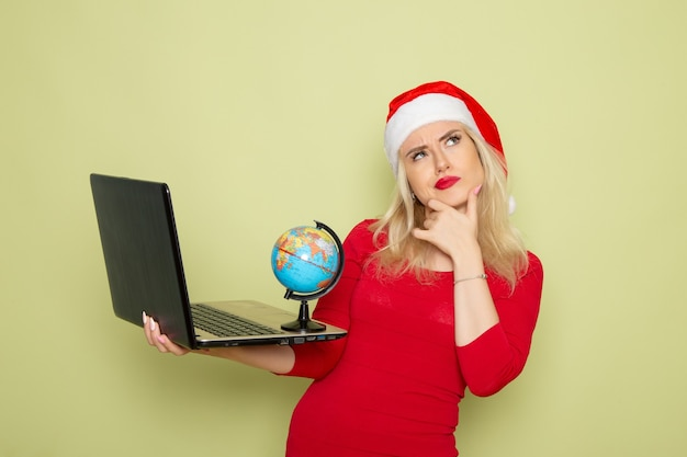 Front view pretty female holding little earth globe and using laptop on green wall christmas color snow holidays new year emotion