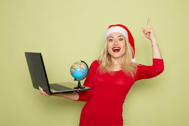 Vista frontale piuttosto femmina che tiene piccolo globo terrestre e utilizzando laptop sulla parete verde natale colore neve capodanno emozione