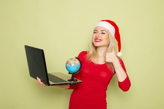 Vista frontale bella femmina che tiene piccolo globo terrestre e utilizzando laptop sul muro verde colore neve vacanze capodanno emozione