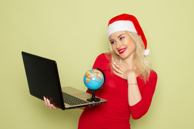 Front view pretty female holding little earth globe and using laptop on green wall holiday christmas snow color
