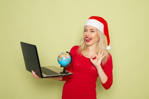 Vista frontale bella femmina che tiene piccolo globo terrestre e utilizzando laptop sul muro verde vacanze emozioni natale neve capodanno colore