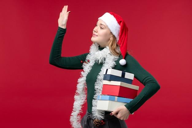 赤い背景に新年のプレゼントを保持している正面図きれいな女性