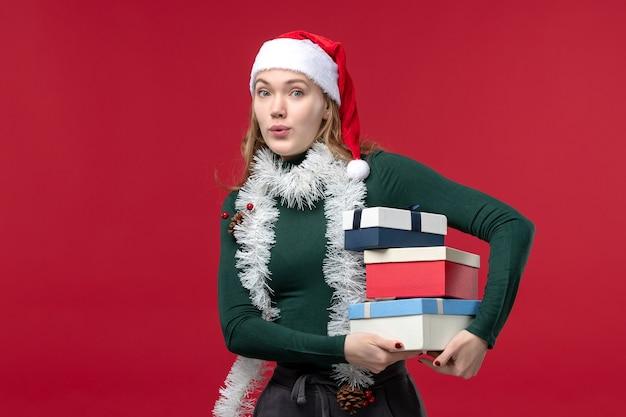 빨간색 배경에 새 해 선물을 들고 전면보기 예쁜 여성