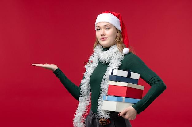 Вид спереди красивая женщина держит новогодние подарки на красном фоне