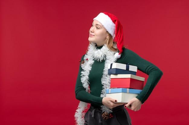 Вид спереди красивая женщина держит новогодние подарки на красном столе