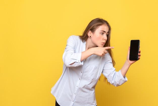 Vista frontale di una bella donna che tiene in mano un telefono