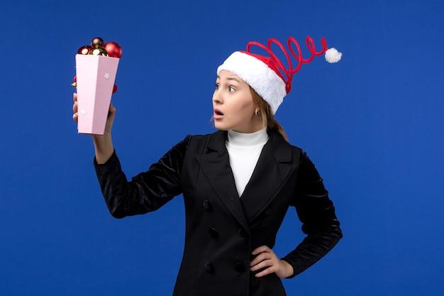 Vista frontale piuttosto femmina che tiene i giocattoli di plastica dell'albero sulla vacanza blu del nuovo anno della parete blu