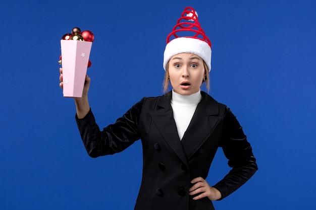 La femmina graziosa di vista frontale che tiene i giocattoli di plastica dell'albero su un blu di festa del nuovo anno della parete blu