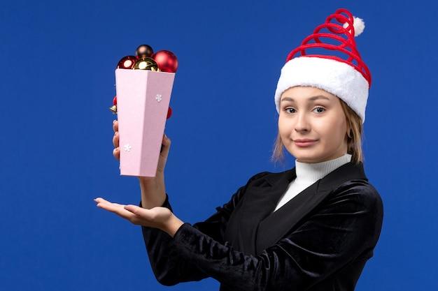 Вид спереди симпатичная женщина держит пластиковые елочные игрушки на синей стене синий новогодний праздник