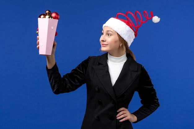 青い壁の青い新年の休日にプラスチックの木のおもちゃを保持している正面図きれいな女性