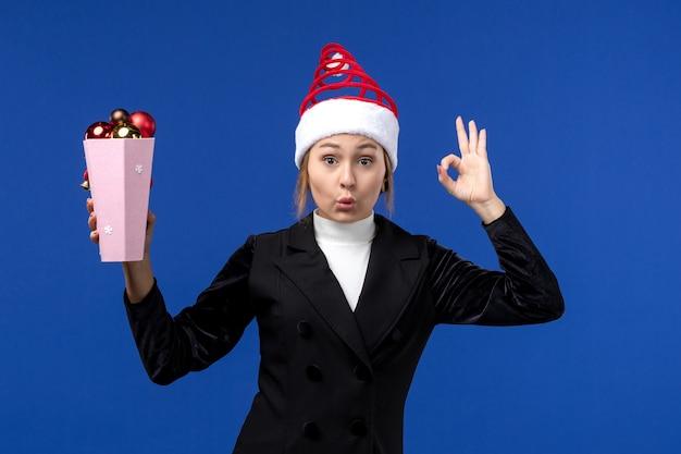 Вид спереди симпатичная женщина держит пластиковые елочные игрушки на синем столе новогодний праздник синий