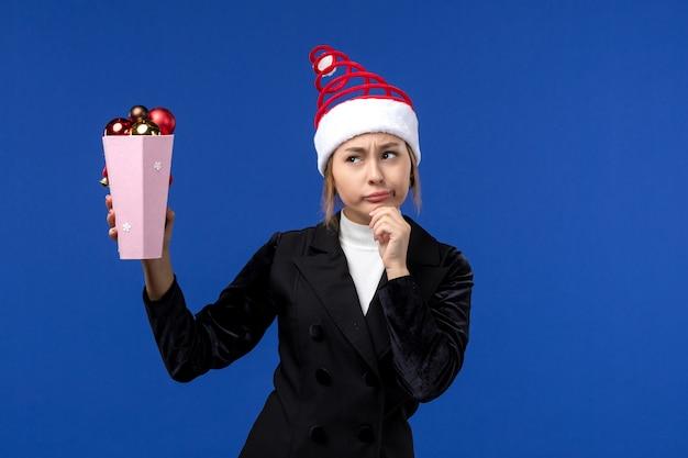 Вид спереди красивая женщина держит пластиковые елочные игрушки на синем столе новогодние праздники синий