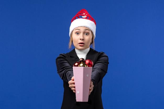 Вид спереди симпатичная женщина держит пластиковые елочные игрушки на синей стене синий праздник новый год