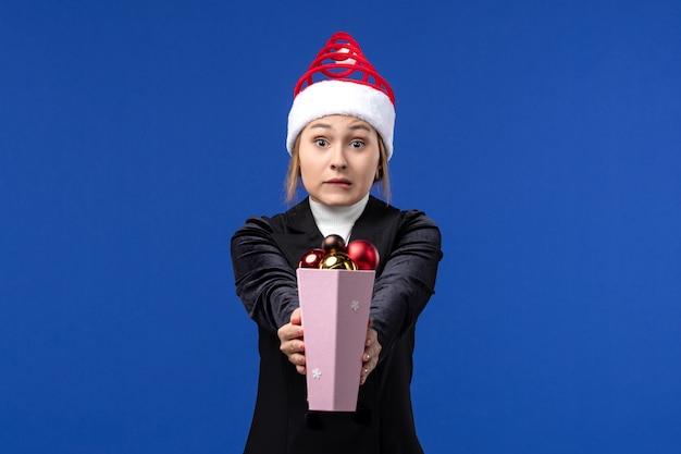 Вид спереди симпатичная женщина держит пластиковые елочные игрушки на синей стене синие праздники новый год