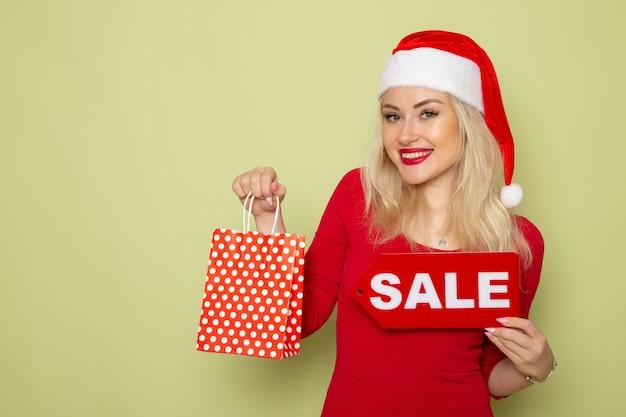 Вид спереди симпатичная женщина, держащая подарок и распродажу, пишет на зеленой стене, снег, эмоции, праздники, рождество, новый год, цвет