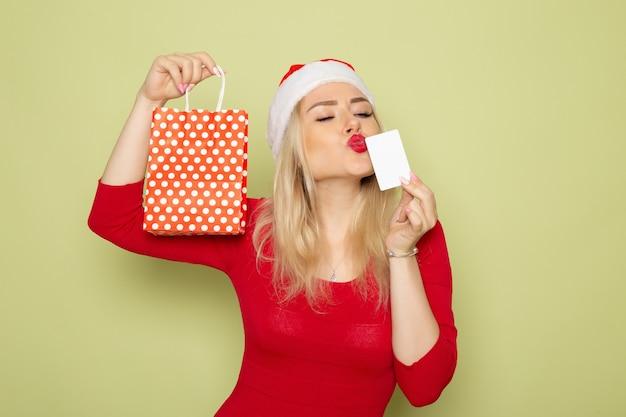 緑の壁の雪の感情の休日のクリスマスの新年の色に小さなパッケージと銀行カードでプレゼントを保持している正面図きれいな女性