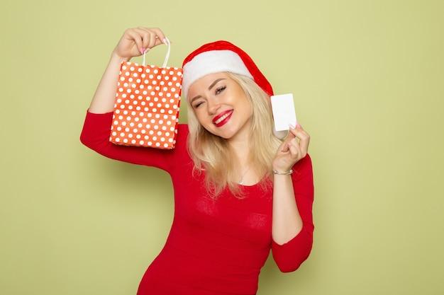 緑の壁の雪の感情の休日の新年の色に小さなパッケージと銀行カードでプレゼントを保持している正面図きれいな女性