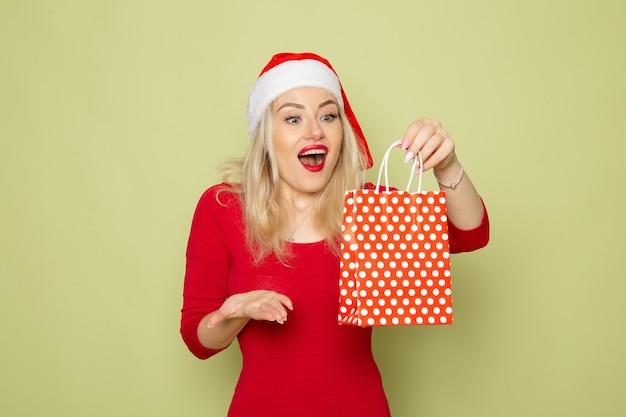 Вид спереди симпатичная женщина, держащая подарок в маленькой упаковке на зеленой стене, праздник, рождество, новогодняя эмоция