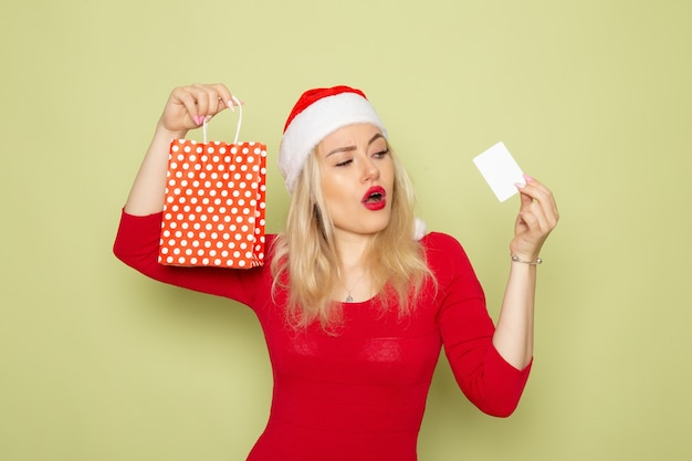 Front view pretty female holding present in little package and bank card on green wall emotions holiday christmas snow color new year
