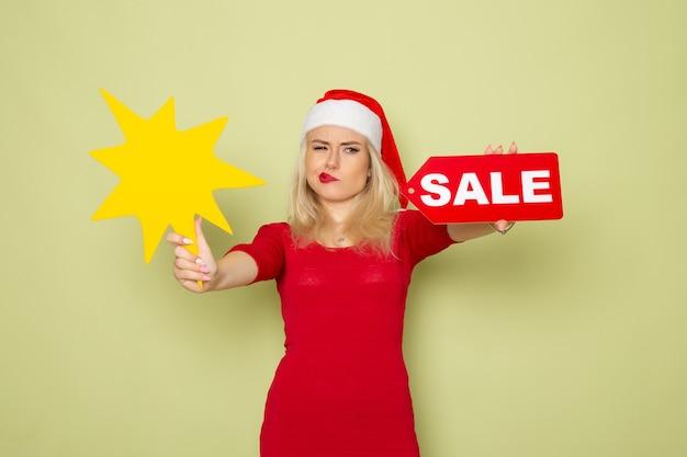 Вид спереди симпатичная женщина, держащая распродажу, и большая желтая фигура на зеленой стене, снежная эмоция, цвет рождества, нового года